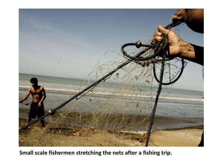 Small scale fishermen stretching the nets after a fishing trip.