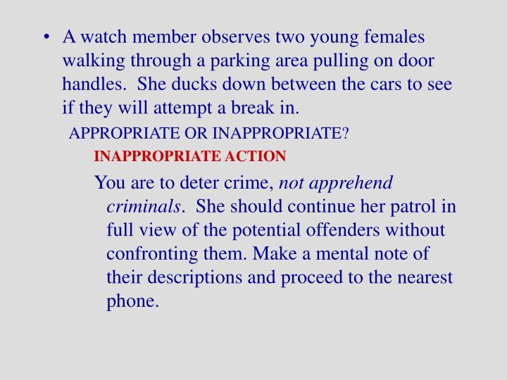 A watch member observes two young females walking through a parking area pulling on door handles.  She ducks down between the cars to see if they will attempt a break in.