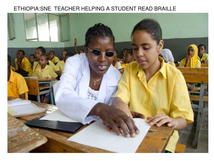 ETHIOPIA:SNE  TEACHER HELPING A STUDENT READ BRAILLE