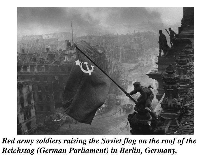 Red army soldiers raising the Soviet flag on the roof of the Reichstag (German Parliament) in Berlin, Germany.
