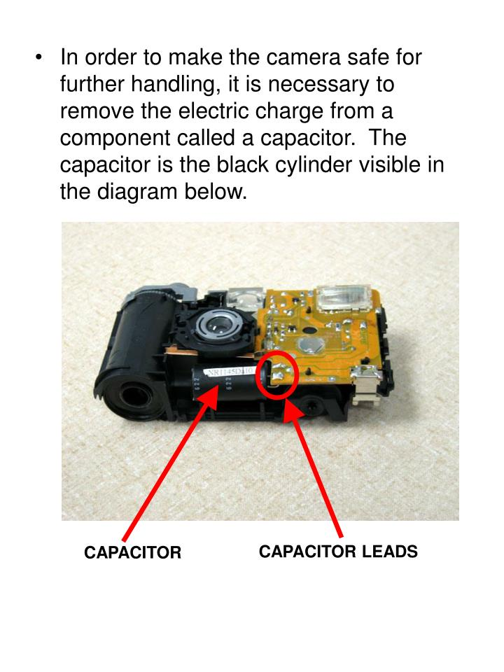 In order to make the camera safe for further handling, it is necessary to remove the electric charge from a component called a capacitor.  The capacitor is the black cylinder visible in the diagram below.