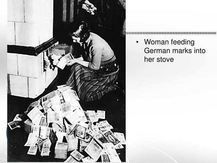 Woman feeding German marks into her stove