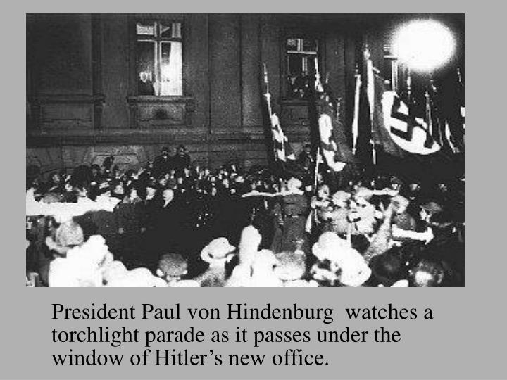 President Paul von Hindenburg  watches a torchlight parade as it passes under the window of Hitler's new office.
