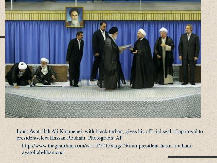 Iran's Ayatollah Ali Khamenei, with black turban, gives his official seal of approval to president-elect Hassan
