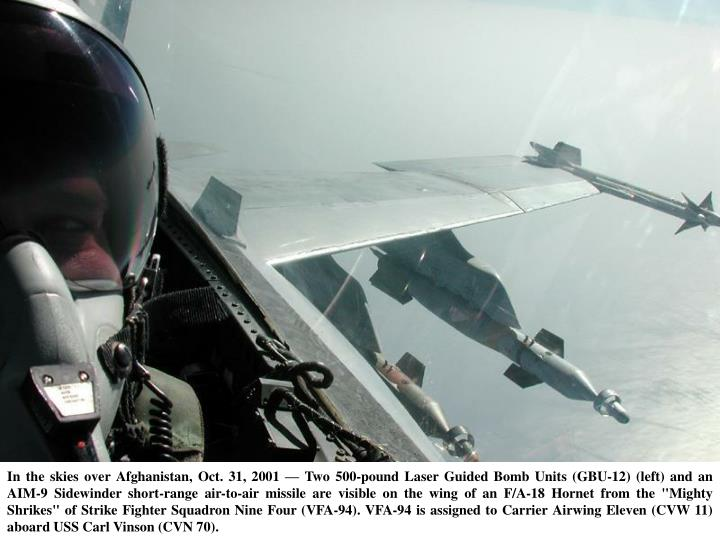 """In the skies over Afghanistan, Oct. 31, 2001 — Two 500-pound Laser Guided Bomb Units (GBU-12) (left) and an AIM-9 Sidewinder short-range air-to-air missile are visible on the wing of an F/A-18 Hornet from the """"Mighty Shrikes"""" of Strike Fighter Squadron Nine Four (VFA-94). VFA-94 is assigned to Carrier Airwing Eleven (CVW 11) aboard USS Carl Vinson (CVN 70)."""