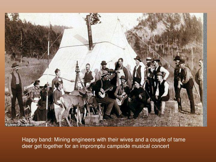 Happy band: Mining engineers with their wives and a couple of tame deer get together for an impromptu campside musical concert
