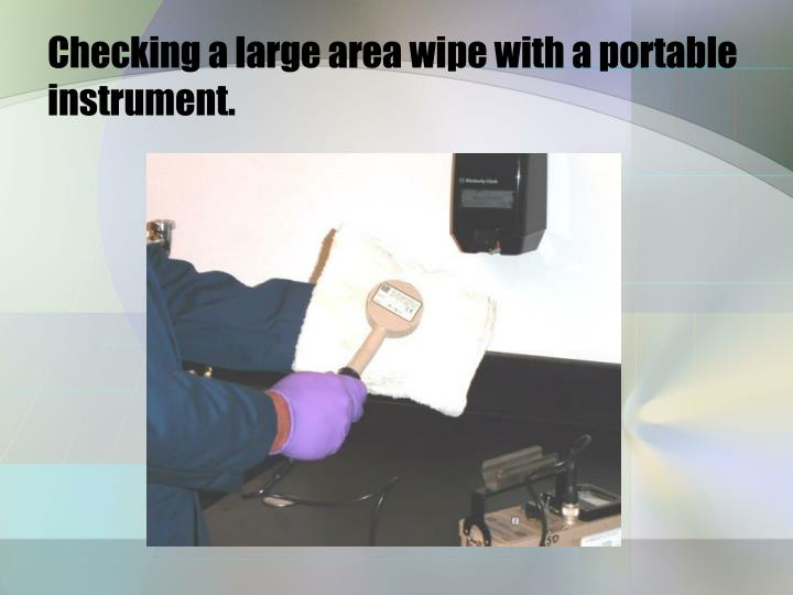 Checking a large area wipe with a portable instrument.