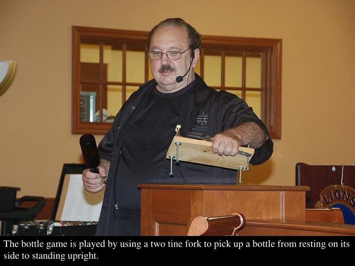 The bottle game is played by using a two tine fork to pick up a bottle from resting on its side to standing upright.