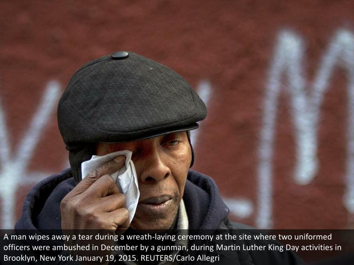A man wipes away a tear during a wreath-laying ceremony at the site where two uniformed officers were ambushed in December by a gunman, during Martin Luther King Day activities in Brooklyn, New York January 19, 2015. REUTERS/Carlo Allegri