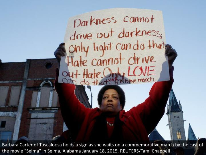 """Barbara Carter of Tuscaloosa holds a sign as she waits on a commemorative march by the cast of the movie """"Selma"""" in Selma, Alabama January 18, 2015. REUTERS/Tami Chappell"""