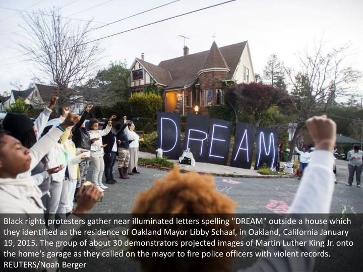 """Black rights protesters gather near illuminated letters spelling """"DREAM"""" outside a house which they identified as the residence of Oakland Mayor Libby Schaaf, in Oakland, California January 19, 2015. The group of about 30 demonstrators projected images of Martin Luther King Jr. onto the home's garage as they called on the mayor to fire police officers with violent records. REUTERS/Noah Berger"""