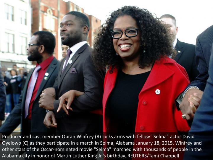 """Producer and cast member Oprah Winfrey (R) locks arms with fellow """"Selma"""" actor David Oyelowo (C) as they participate in a march in Selma, Alabama January 18, 2015. Winfrey and other stars of the Oscar-nominated movie """"Selma"""" marched with thousands of people in the Alabama city in honor of Martin Luther King Jr.'s birthday. REUTERS/Tami Chappell"""