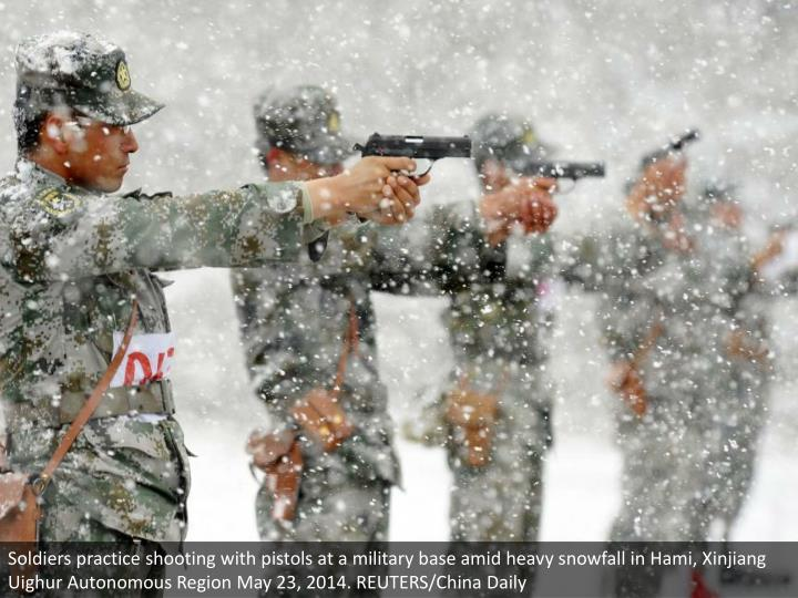 Soldiers practice shooting with pistols at a military base amid heavy snowfall in Hami, Xinjiang Uighur Autonomous Region May 23, 2014. REUTERS/China Daily