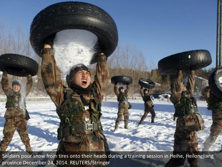 Soldiers pour snow from tires onto their heads during a training session in Heihe, Heilongjiang province December 24, 2014. REUTERS/Stringer