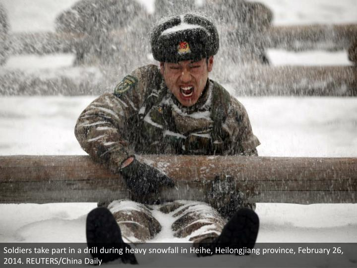 Soldiers take part in a drill during heavy snowfall in Heihe, Heilongjiang province, February 26, 2014. REUTERS/China Daily