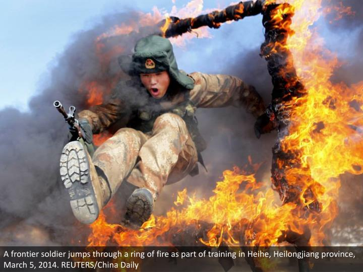 A frontier soldier jumps through a ring of fire as part of training in Heihe, Heilongjiang province, March 5, 2014. REUTERS/China Daily