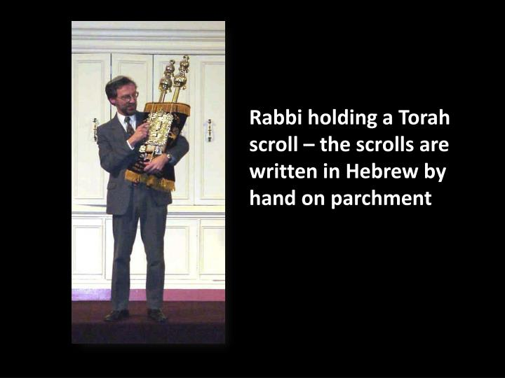 Rabbi holding a Torah scroll – the scrolls are written in Hebrew by hand on parchment