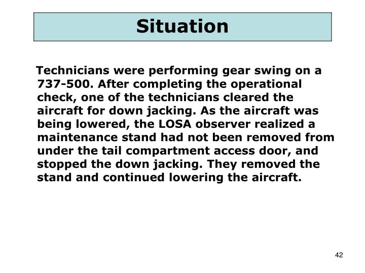 Technicians were performing gear swing on a 737-500. After completing the operational check, one of the technicians cleared the aircraft for down jacking. As the aircraft was being lowered, the LOSA observer realized a maintenance stand had not been removed from under the tail compartment access door, and stopped the down jacking. They removed the stand and continued lowering the aircraft.