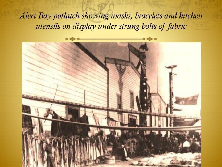 Alert Bay potlatch showing masks, bracelets and kitchen utensils on display under strung bolts of fabric