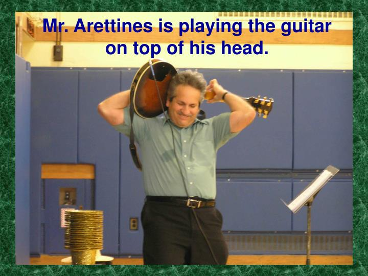Mr. Arettines is playing the guitar on top of his head.