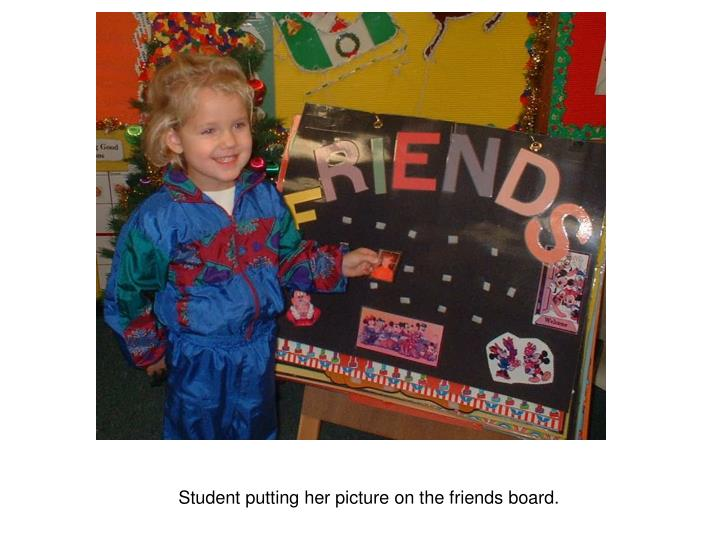 Student putting her picture on the friends board.
