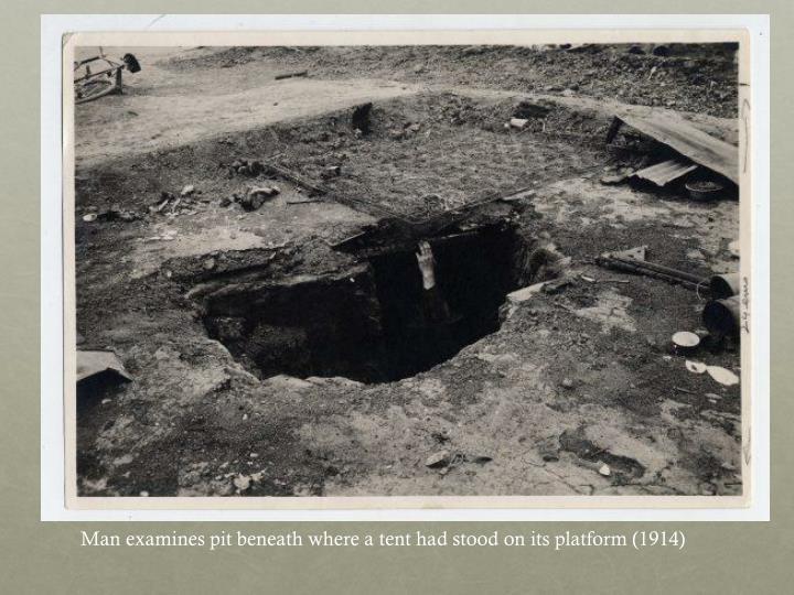 Man examines pit beneath where a tent had stood on its platform (1914)
