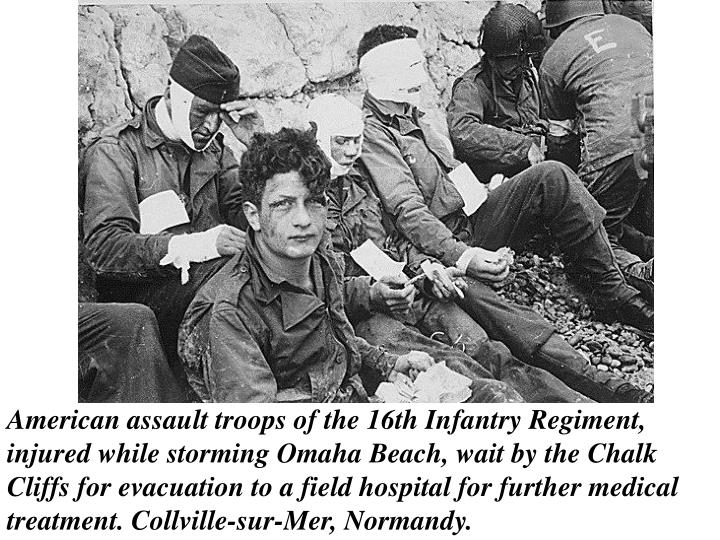 American assault troops of the 16th Infantry Regiment, injured while storming Omaha Beach, wait by the Chalk Cliffs for evacuation to a field hospital for further medical treatment. Collville-sur-Mer, Normandy.
