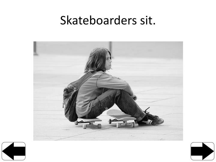 Skateboarders sit.