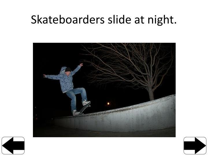 Skateboarders slide at night.