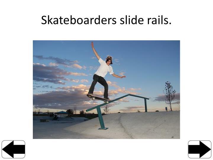 Skateboarders slide rails.