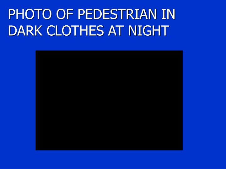 PHOTO OF PEDESTRIAN IN DARK CLOTHES AT NIGHT