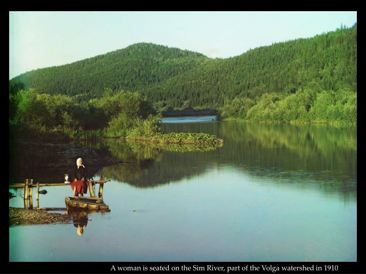 A woman is seated on the Sim River, part of the Volga watershed in 1910